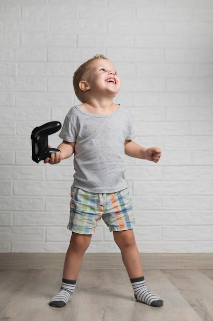 Het gelukkige jongen spelen met bedieningshendel thuis Gratis Foto