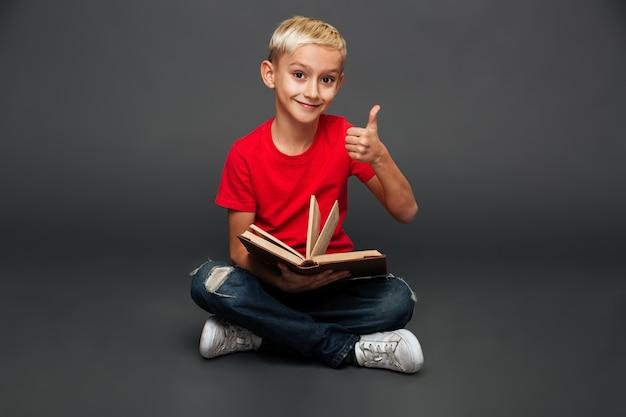 Het gelukkige kleine de lezingsboek van het jongenskind tonen beduimelt omhoog. Gratis Foto