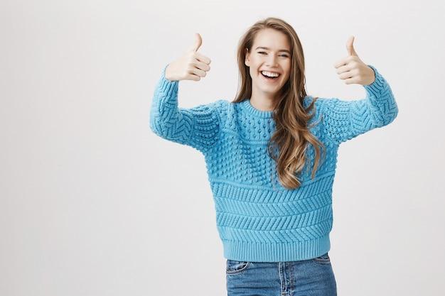 Het gelukkige lachende meisje duim-omhoog, houdt van en keurt goed Gratis Foto