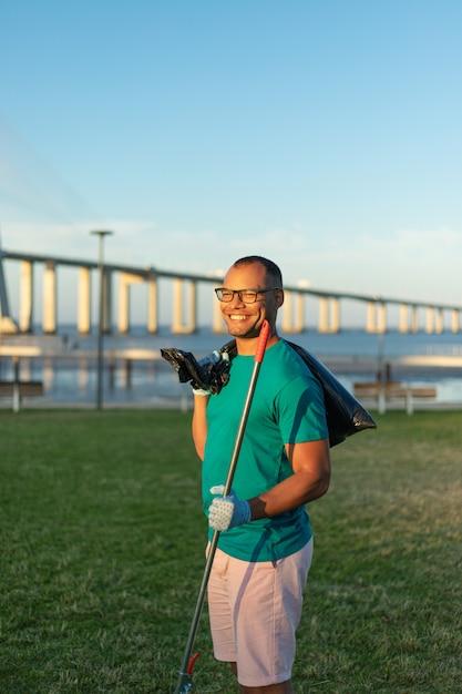 Het gelukkige mannelijke vrijwilliger stellen in stadspark Gratis Foto