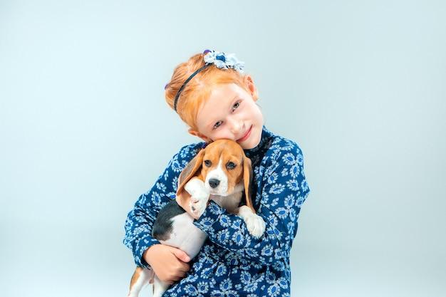 Het gelukkige meisje en een beagle puppie op grijze muur Gratis Foto