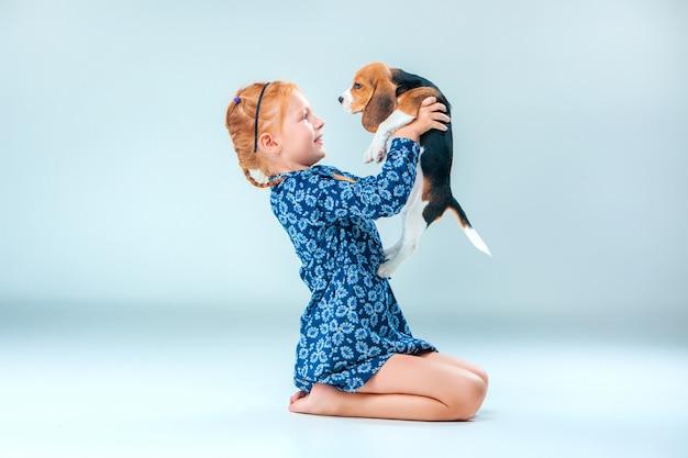 Het gelukkige meisje en een brakpuppy op grijze muur Gratis Foto