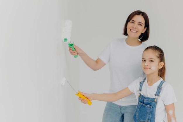 Het gelukkige meisje en haar moeder schilderen muren in witte kleur gebruikend verfrollen Premium Foto