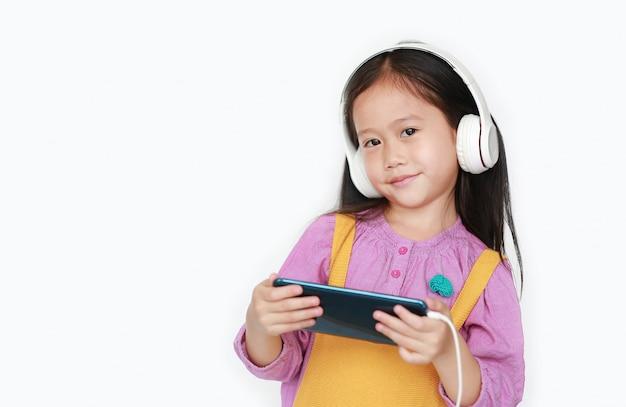 Het gelukkige meisje geniet van luister muziek met hoofdtelefoons door smartphone die over wit wordt geïsoleerd. Premium Foto