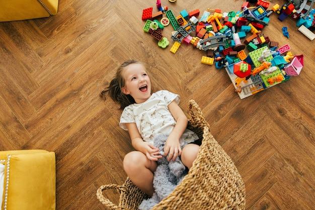 Het gelukkige meisje goot blokken op de vloer en ligt in een mand en lacht. speeltijd en rommel in de kinderkamer Premium Foto