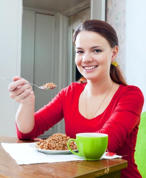 Het gelukkige meisje in rood eet boekweit Gratis Foto