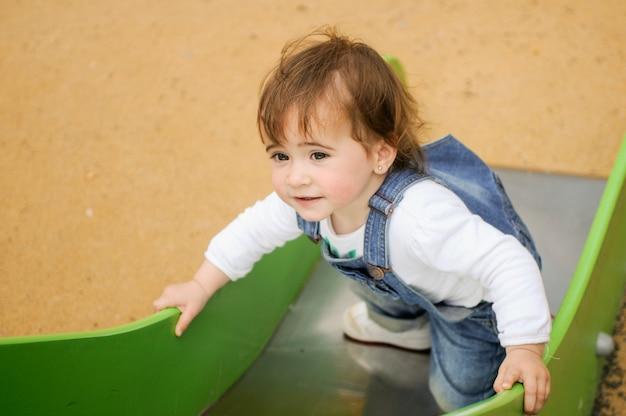 Het gelukkige meisje spelen in een stedelijke speelplaats. Gratis Foto