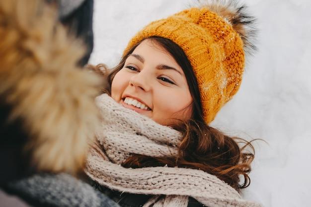 Het gelukkige paar bij bosaardpark in koud seizoen. gelukkig donkerbruin meisje in gele hoed Premium Foto