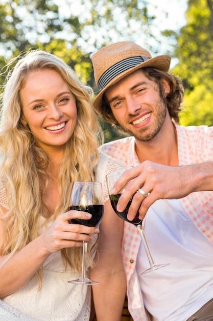 Het gelukkige paar die een picknick hebben en drinkt rode wijn in de tuin Premium Foto