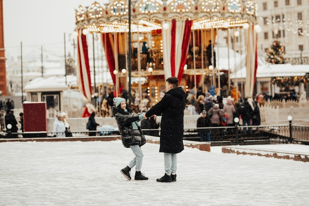 Het gelukkige paar loopt door een pretpark in de winter Premium Foto