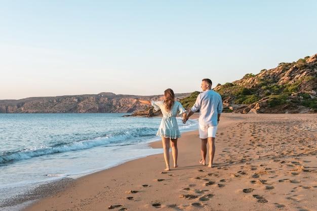 Het gelukkige paar loopt op het strand tijdens zonsondergang of zonsopgang. Premium Foto