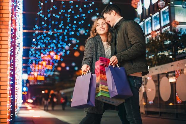 Het gelukkige paar met boodschappentassen genieten van de nacht in de stad Gratis Foto