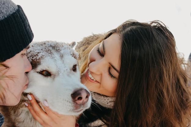 Het gelukkige paar met hondhaski bij bosaardpark in koud seizoen. reisavontuur liefdesverhaal Premium Foto