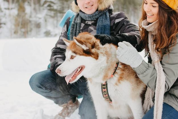 Het gelukkige paar met hondhaski bij bosaardpark in koud seizoen Premium Foto