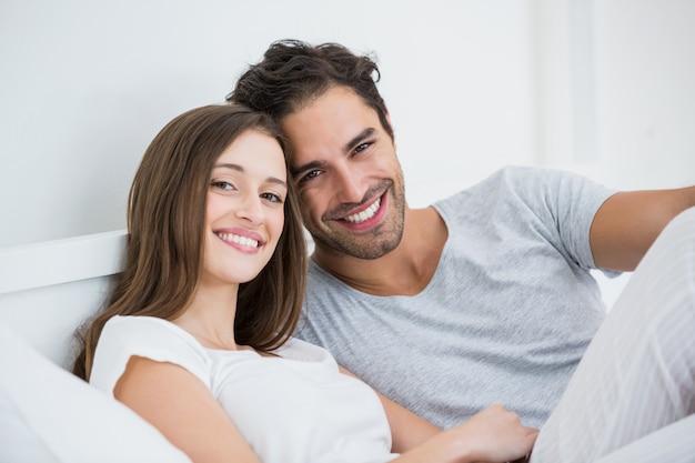 Het gelukkige paar ontspannen op bed Premium Foto