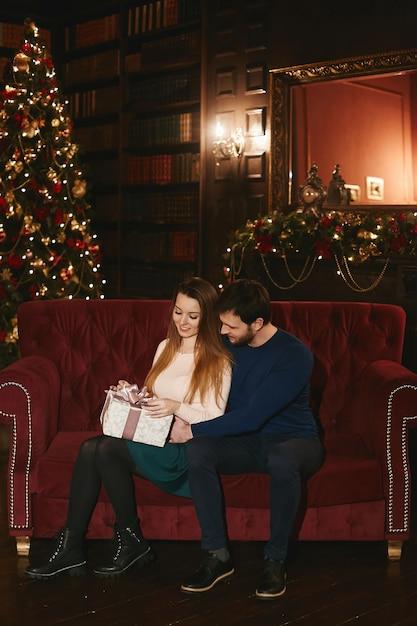 Het gelukkige paar zit op de rode laag, knappe man die modelvrouw omhelst die de doos van de kerstmisgift houdt Premium Foto
