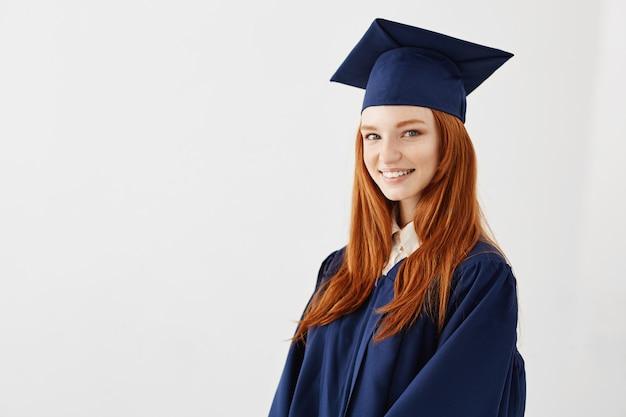 Het gelukkige roodharige vrouwelijke gediplomeerde glimlachen. Gratis Foto