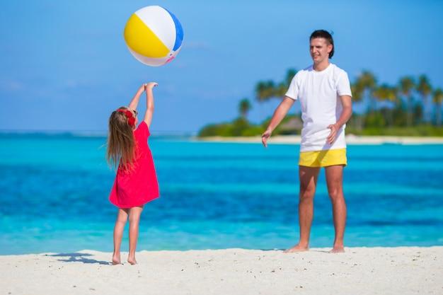 Het gelukkige vader en dochter spelen met bal die pret openlucht op strand hebben Premium Foto