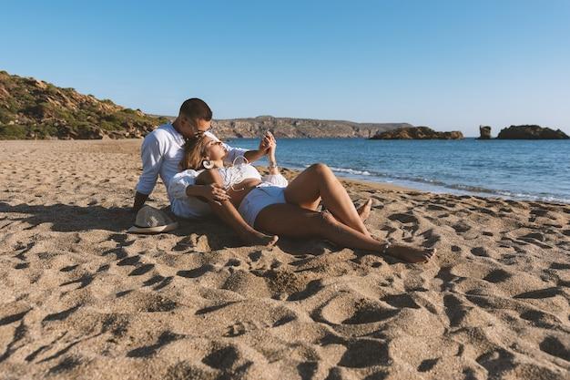 Het gelukkige verliefde paar, zit op het strand tijdens zonsondergang of zonsopgang. Premium Foto