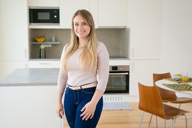 Het gelukkige vrij eerlijke haired jonge vrouw stellen in keuken Gratis Foto