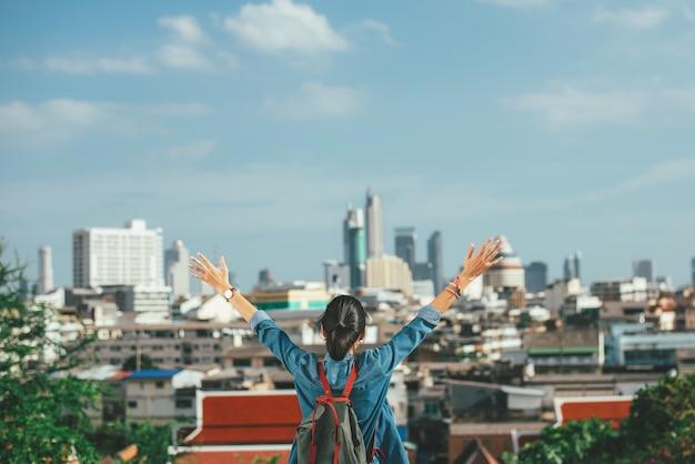 Het gelukkige vrouwenreiziger verhogen dient de achtergrond van de stadsscène met exemplaarruimte in Premium Foto