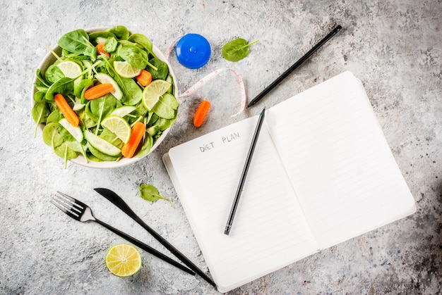 Het gewicht van het dieetplan verliest de salade van de concepten verse groente met van de de notepadgrey steen van het vorkmes de lijst Premium Foto