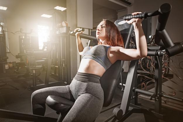 Het gewichtheffen van de geschiktheidsvrouw training in gymnastiek Gratis Foto
