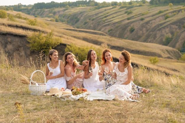 Het gezelschap van prachtige vrienden die plezier hebben, wijn drinken en genieten van een picknick in het heuvellandschap Premium Foto