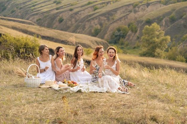 Het gezelschap van prachtige vriendinnen die plezier hebben, wijn drinken en genieten van een picknick in de heuvels Premium Foto