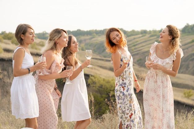 Het gezelschap van prachtige vrouwelijke vrienden die plezier hebben en genieten van een zomerse groene picknick, dans en alcohol drinken. mensen concept. Premium Foto