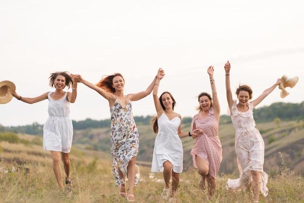 Het gezelschap van vrolijke vriendinnen beleeft een geweldige tijd samen op een picknick op een schilderachtige plek met uitzicht op de groene heuvels. meisjes in witte jurken dansen in het veld Premium Foto