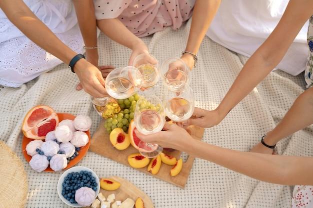 Het gezelschap van vrouwelijke vrienden geniet van een zomerpicknick en hef glazen met wijn Premium Foto