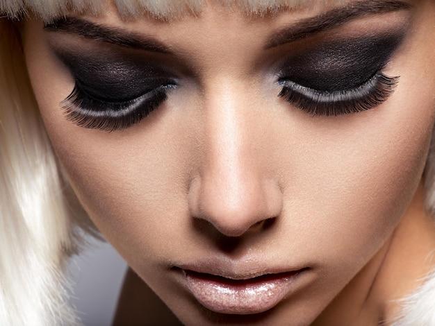 Het gezichtsclose-up van het meisje met lange zwarte wimpers. mode make-up Gratis Foto