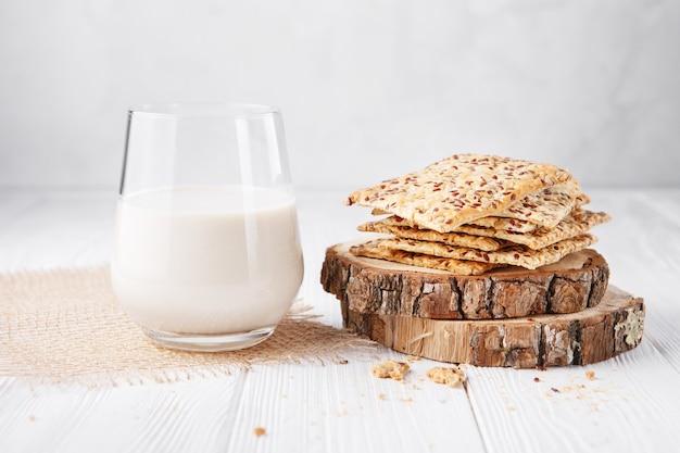 Het glas lactosevrije plantaardige melk: soja-, rijst-, haver- of amandelmelk en koekjes met sesamzaadjes Premium Foto