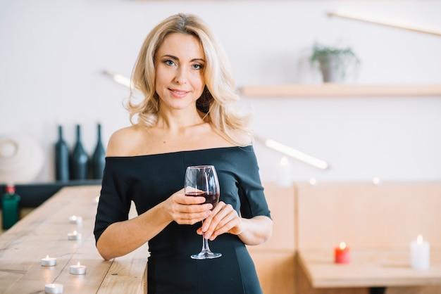 Het glas van de vrouwenholding van wijn en het onder ogen zien van camera Gratis Foto