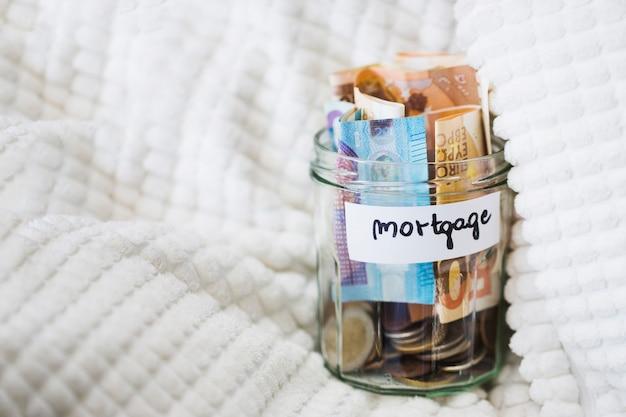 Het glaskruik van de hypotheek met euro nota's en muntstukken op witte deken Gratis Foto