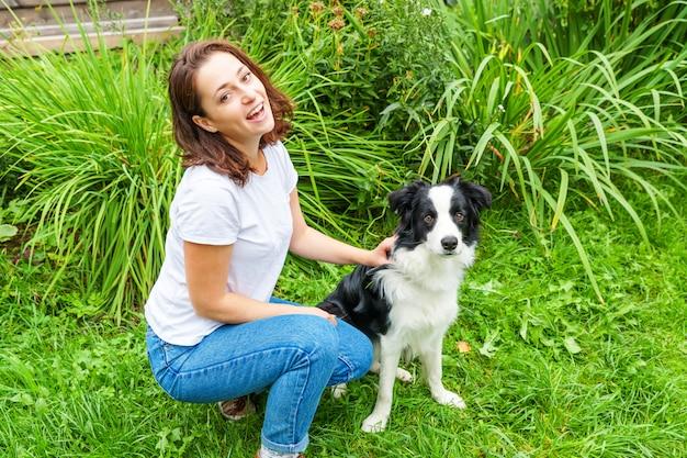 Het glimlachen het jonge aantrekkelijke vrouw spelen met leuke puppyhond border collie in de zomertuin of stadspark. meisje training truc met hond vriend. dierenverzorging en dieren concept. Premium Foto