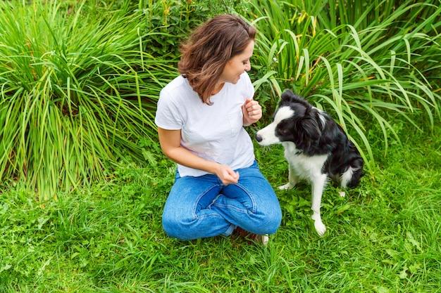 Het glimlachen het jonge aantrekkelijke vrouw spelen met leuke puppyhond border collie in de zomertuin of stadspark openlucht. meisje training truc met hond vriend. dierenverzorging en dieren concept. Premium Foto