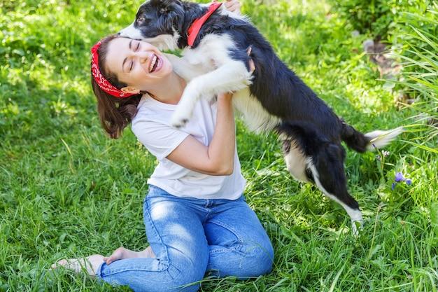 Het glimlachen het jonge aantrekkelijke vrouw spelen met leuke puppyhond border collie in tuin of stadspark Premium Foto