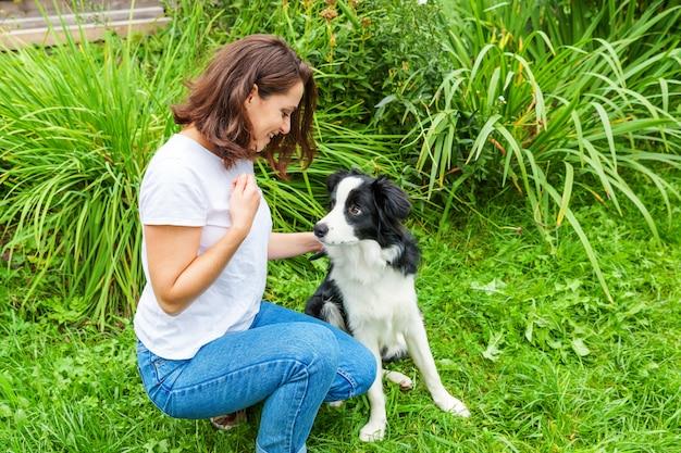 Het glimlachen het jonge aantrekkelijke vrouw spelen met leuke puppyhond border collie op de zomertuin of de openluchtachtergrond van het stadspark. meisje training truc met hond vriend. dierenverzorging en dieren concept. Premium Foto