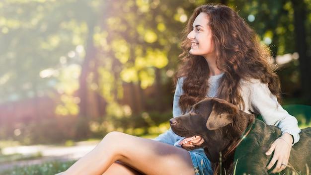 Het glimlachen jonge vrouwenzitting met haar hond in tuin Gratis Foto
