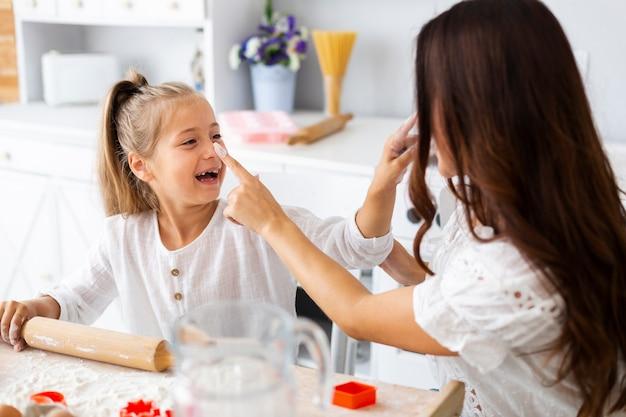 Het glimlachen meisje het koken met haar moeder Gratis Foto