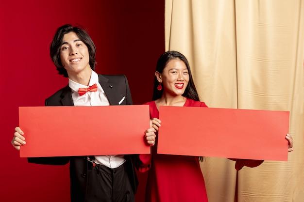 Het glimlachen paar het stellen met rode enveloppen voor chinees nieuw jaar Gratis Foto