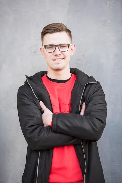 Het glimlachen portret van een jonge mens die zwart jasje met zijn die wapens dragen tegen concrete achtergrond worden gekruist Gratis Foto