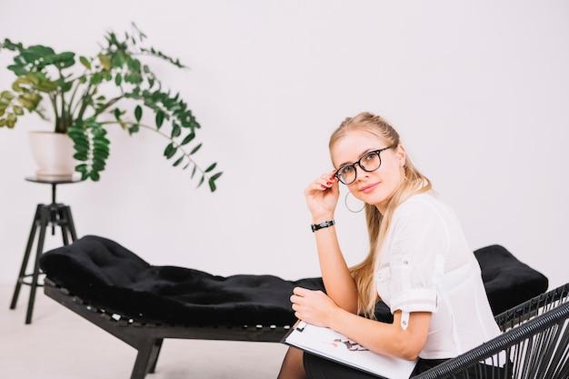 Het glimlachen portret van een mooie psycholoogzitting op stoel met klembord in het bureau Gratis Foto