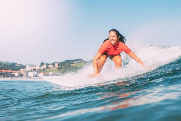 Het glimlachen tiener surfen, gefotografeerd van het water, op een zonnige dag Premium Foto