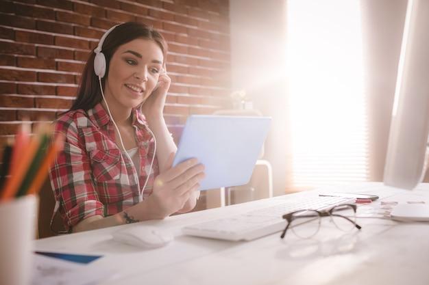 Het glimlachen uitvoerende het luisteren muziek op digitale tablet Premium Foto