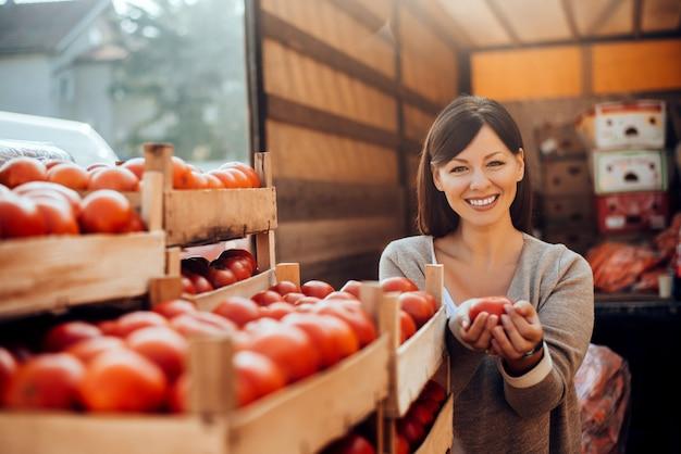 Het glimlachen van de groenten van de vrouwenholding bij groene markt. Premium Foto