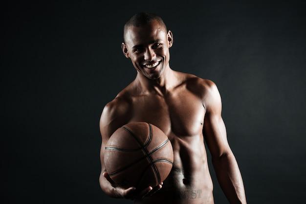 Het glimlachen van de jonge bal van de de spelerholding van het afro amerikaanse basketbal Gratis Foto
