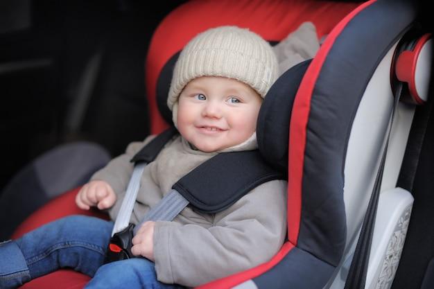 Het glimlachen van de zitting van de peuterjongen in autozetel Premium Foto